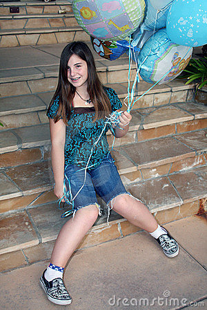 Teen girl holds bunch of balloons