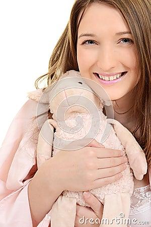 Teen girl hugging toy lamb