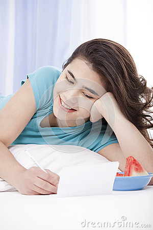 Teen girl lying on floor writing a letter or note
