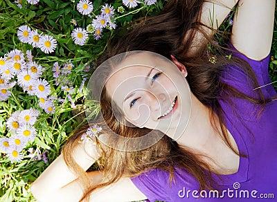 Teen girl lying in grass