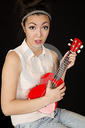 Free Teen Girl Model Playing A Ukulele With A Fun Facial Expression Royalty Free Stock Photo - 52032745