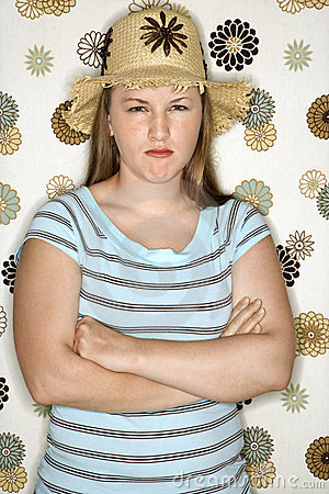 Teen girl pouting with arms crossed.