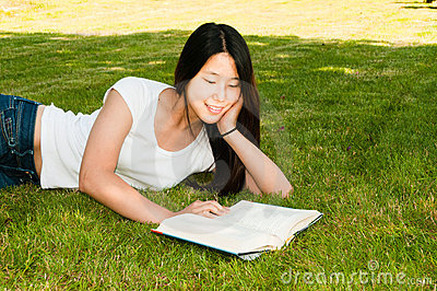 Teen Girl Reading Book on Grass