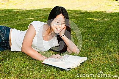 Teen Girl Reading Book on Grass