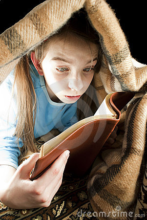 Teen girl reading book under blanket