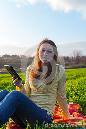 Teen girl reading electronic book outdoors