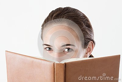 Teen girl reading, looking over the book