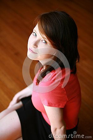 Teen girl seated on wood floor