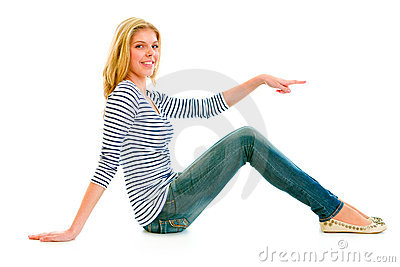 Teen girl sitting on floor and pointing finger