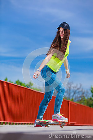 Teen girl skater riding skateboard on street. Stock Photo