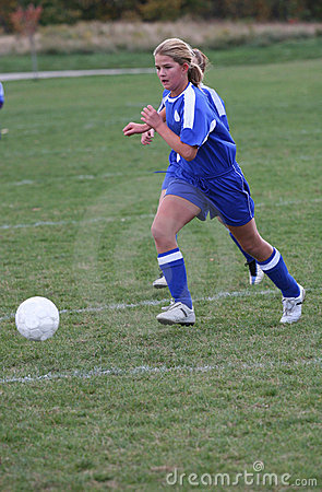 Teen Girl Soccer Player Chasing Ball