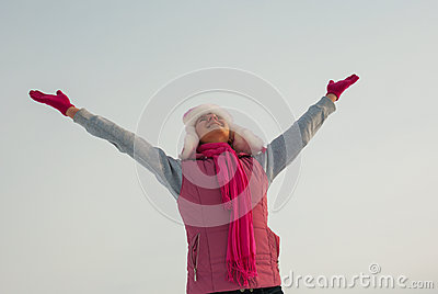 Teen girl staying with raised hands