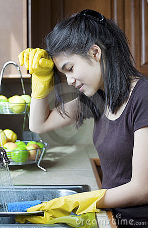 Teen girl washing dishes at kitchen sink, tired