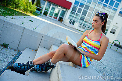Teen girl wearing roller skates with book