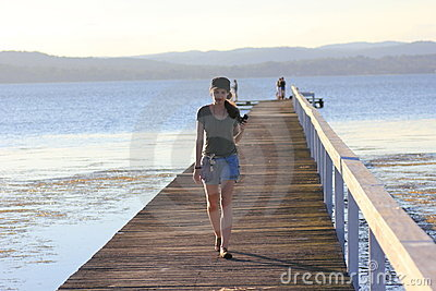 Jetty at lake with young woman