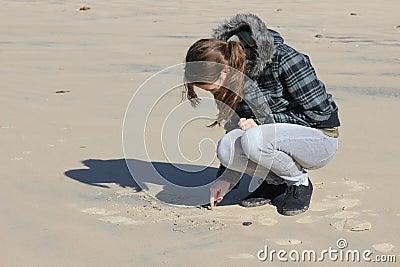 Teen girl writing in sand