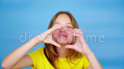 Teen girl in a yellow t-shirt is looking at camera, blows a kiss and showing heart shape. Blue background with copy space. Teenager emotions. 4k footage stock video footage