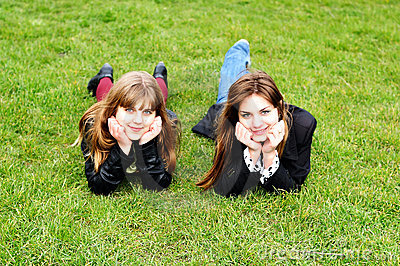 Teen girls laying on the green grass