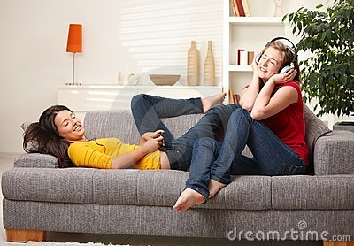 Teen girls listening to music on couch