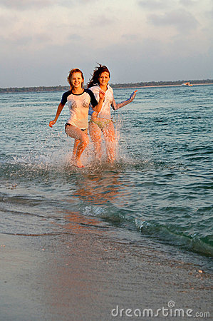 Teen girls running at beach