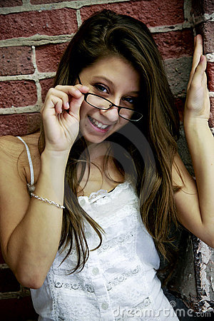 Teen with glasses by brick wall