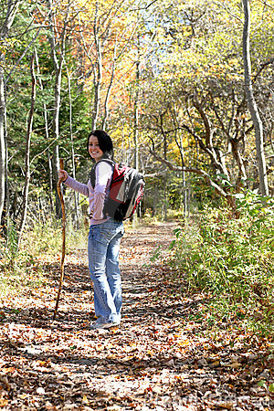 Teen with hiking stick pauses on the trail