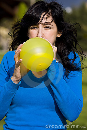 Teen inflating yellow balloon
