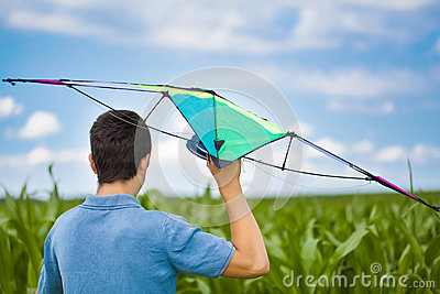 Teen with kite on a corn field