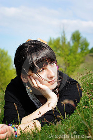 Teen lying on grass thinking