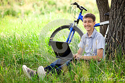 Teen in park with new laptop