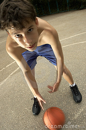 Teen plays in basketball on the street