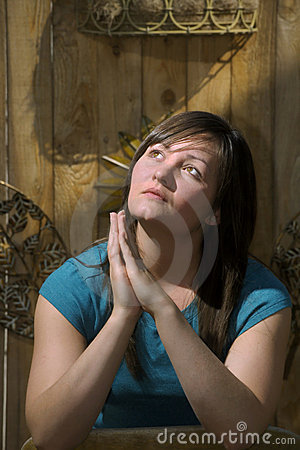 Teen prays by garden fence