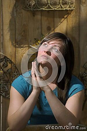 Teen prays by garden fence
