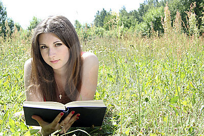 Teen reading in meadow