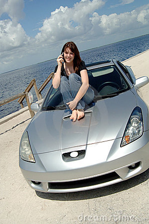Teen sitting on car hood on cell phone
