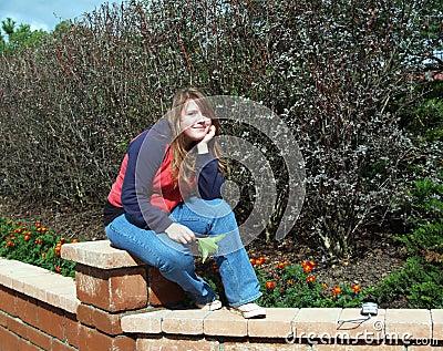 Teen sitting on the garden jamb
