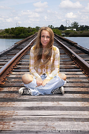 Teen sitting on train tracks