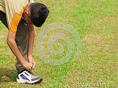 Teen tying his shoe