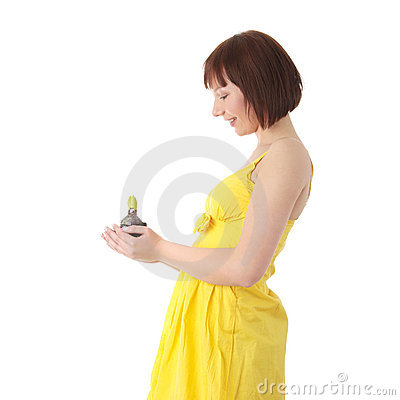 Teen woman in yellow dress holding small plant