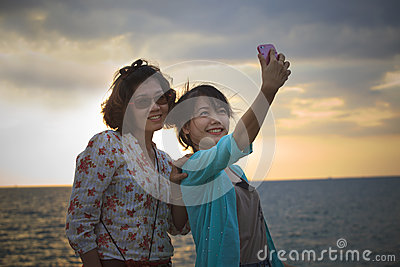 Teen and young woman take a photo by mobile phone at sea side
