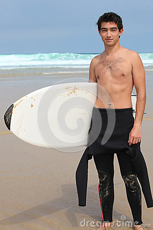 Teenage boy  holding surfboard