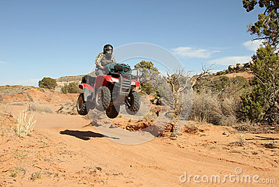 Teenage boy driving All Terrain Vehicle (ATV).