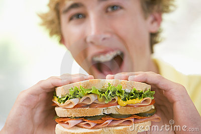 Teenage Boy Eating Sandwich