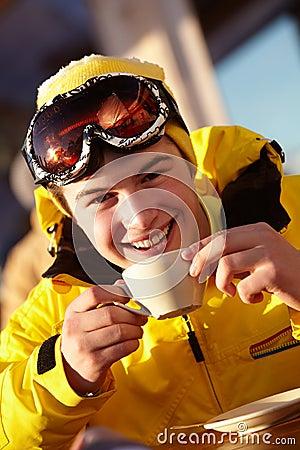 Teenage Boy Enjoying Hot Drink In Cafe