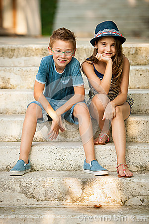 Teenage boy and girl sitting on stairs in park Stock Photo