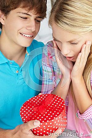 Teenage boy giving gift to girl