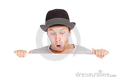 Teenage boy hiding behind a billboard