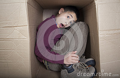Teenage boy hiding in cardboard box