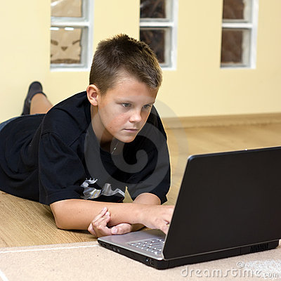 Teenage boy and laptop on floor
