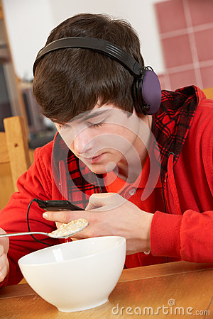 Teenage Boy Listening To MP3 Player Whilst Eating